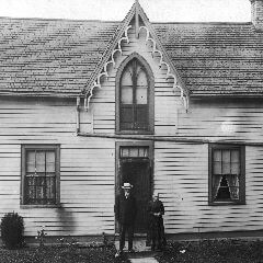 A cropped black and white photograph of an old couple standing in front of their wooden house with a high, ornately trimmed gable.
