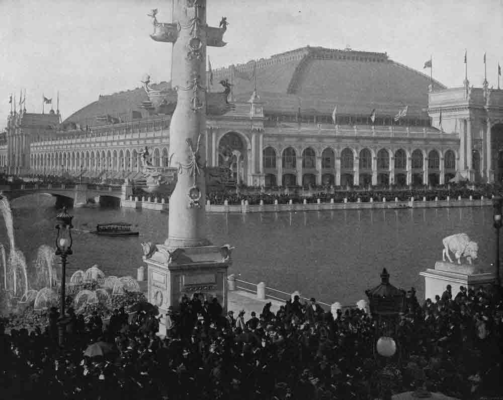 A black and white photograph of an ornate building with an arcade of columns across a body of water.