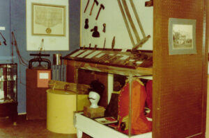 A colour photograph with a yellowed tint of a group of historical items on display.