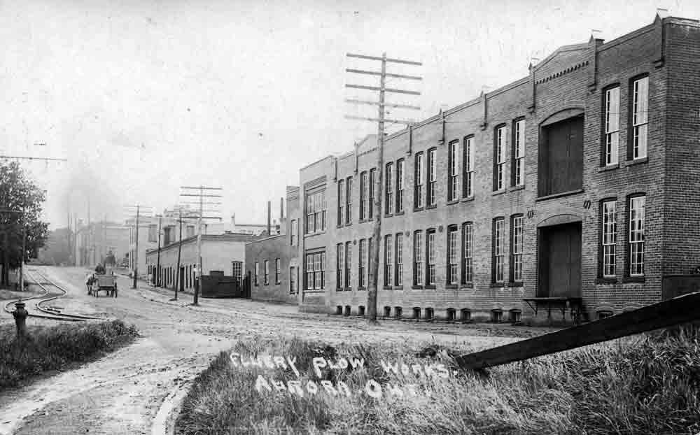 A black and white image of a street with a gentle slope up and a large industrial brick building on the right side.
