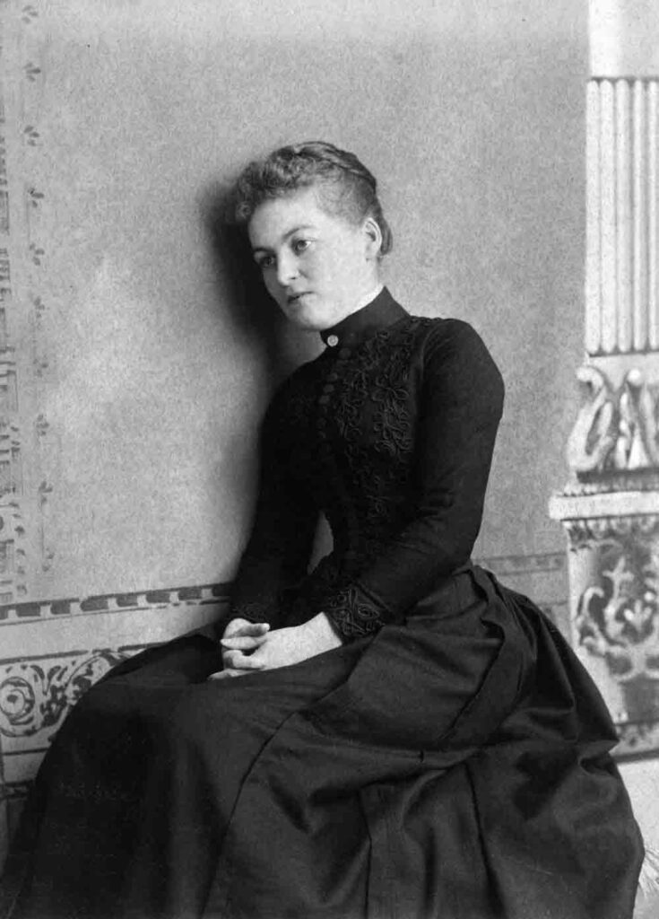 A black and white photograph of a woman in a high-collared black dress sitting against a painted backdrop.