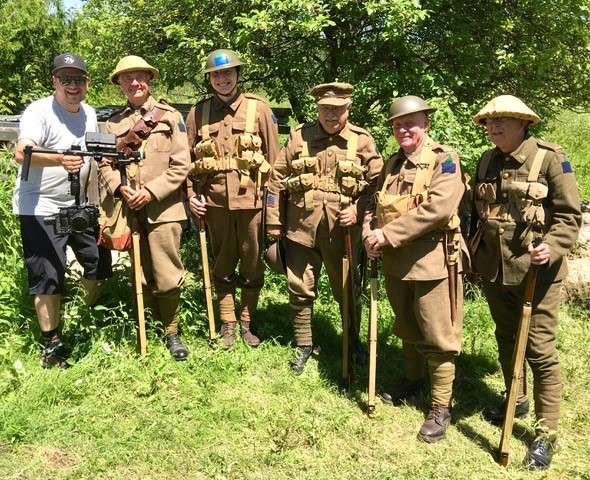 A group of older World War 1 re-enactors in full uniform with rifles pose with a videographer holding a camera in a stabilization rig.