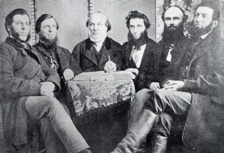 A black and white photograph of a group of 6 men sitting dressed in mid-19th century style.