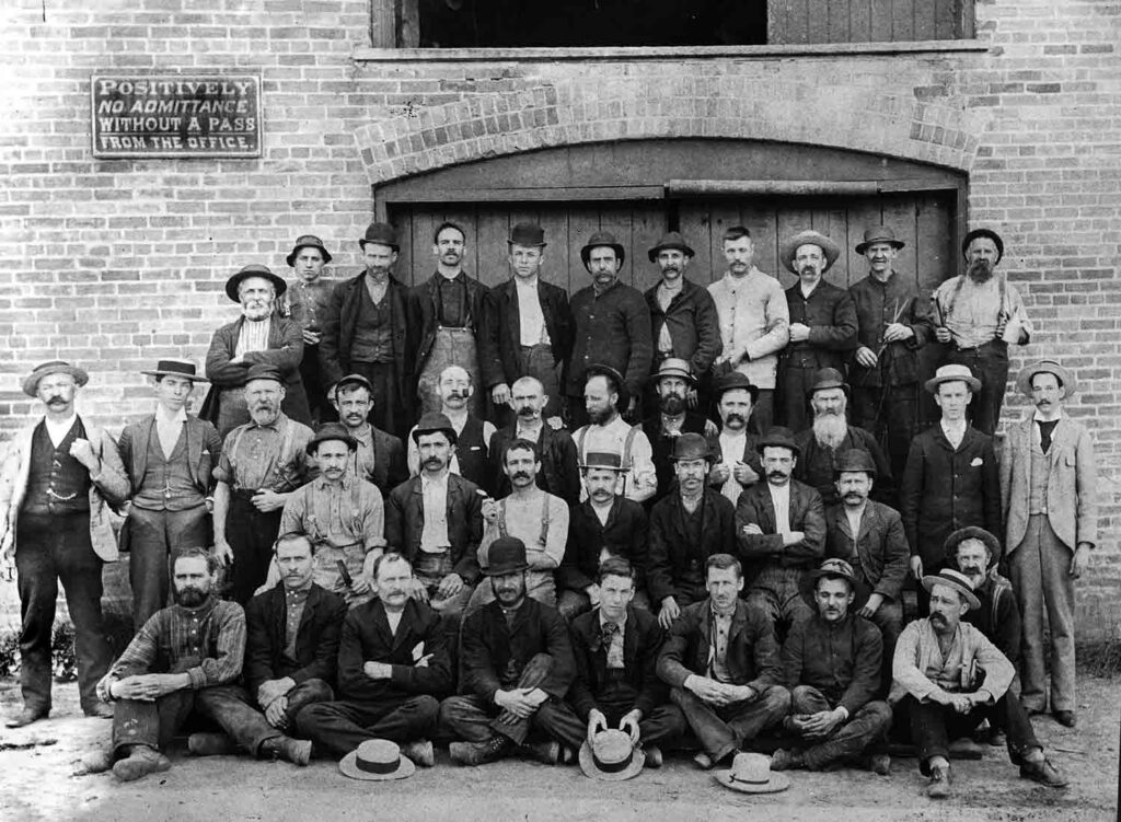 A black and white photograph of a group of men in a variety of late 19th century dress standing in front of a large pair of factory doors.