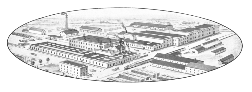 An oval-shaped aerial view drawing of a large factory complex of white buildings with grey roofs.