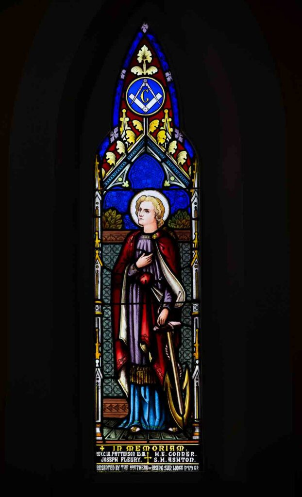 A photograph of a stained glass window against a black background, a masonic symbol at the top.