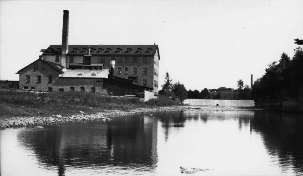 A black and white photograph of a brick factory building adjacent to a pond or river.
