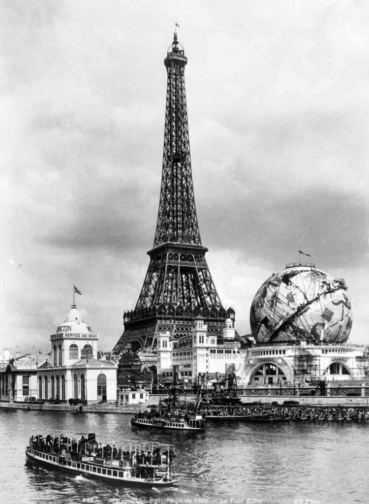 A black and white photograph of the Eiffel Tower beside a globe-shaped structure, and in front of a river with boats traversing.
