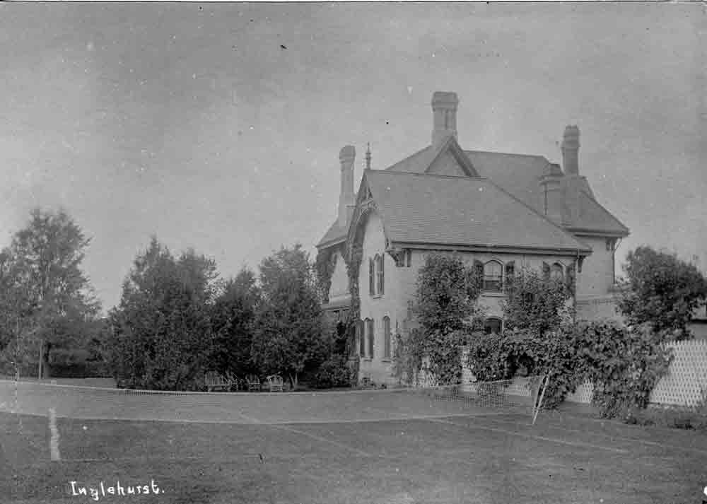 A black and white photograph of a grass tennis court on the lawn of stately mansion.