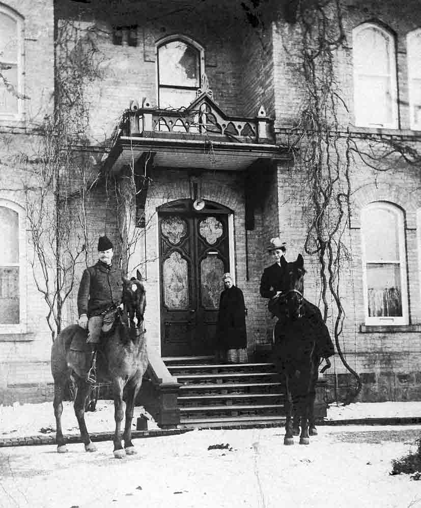 A black and white photograph of a man and woman each on a horse in front of the porch of a large house, a woman stands in front of the door.