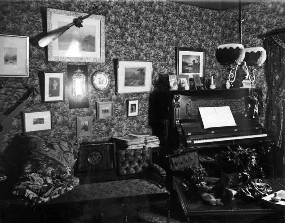 A black and white photograph of the interior of busily decorated room with an upright piano in the corner.