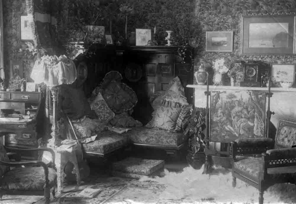 A black and white photograph of the interior of a busily decorated room, with a complex multi-seated chair in the corner.