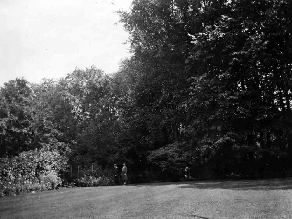 A black and white photograph of two figures standing at the edge of a small garden at the end of a large lawn.