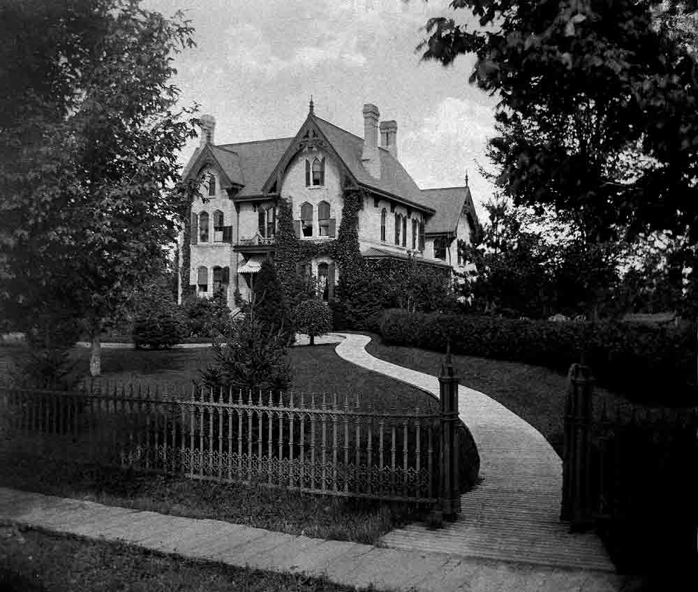 A black and white photo of an ornate mansion with dark roof and trim in its yard with a winding path to the entrance.