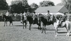 Black and white photo of five boys in suits riding ponies.