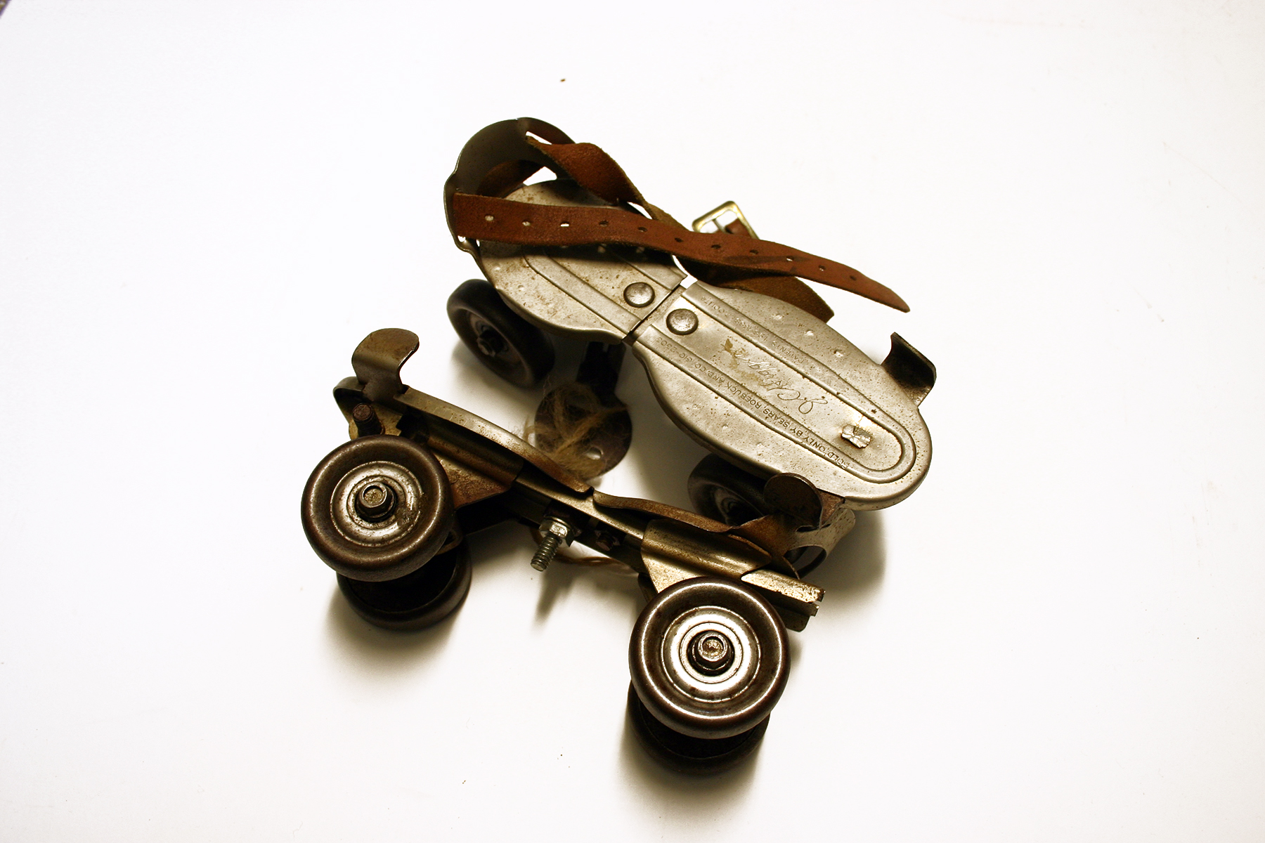 An old pair of leather-strapped roller skates, photographed on a white background.