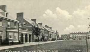 A black and white photograph postcard of a row of brick buildings with a large school building at the end of the road, sapling trees line the lawn in front.