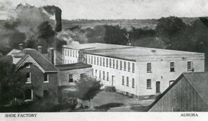 A black and white photograph of a long, light-coloured industrial building, a dark smokestack in the rear is producing smoke.