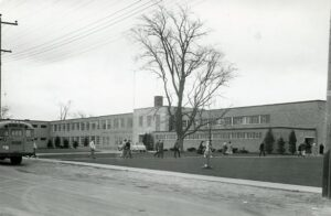 A black and white photograph of students streaming into a long brick school building from a bus parked on the street.