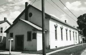 A black and white photograph of a meeting hall with a small circular window over the entrance, a hydro pole and street sign are in the foreground.
