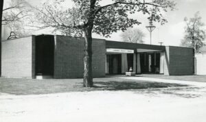 A black and white photograph of a plain low brick library building with a tree in front.