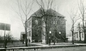 A black and white photograph of a square shaped brick school building with arched door and windows, students stand around the yard with leafless trees.
