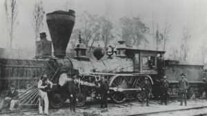 A black and white photograph of a steam engine with an oversized stack, with a group of men posing in front of it, one sits on the pilot, two men are inside the engine's cab leaning out.