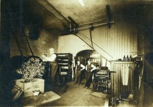 A black and white photograph of the interior of a newspaper print shop, with one man working and two men posing.