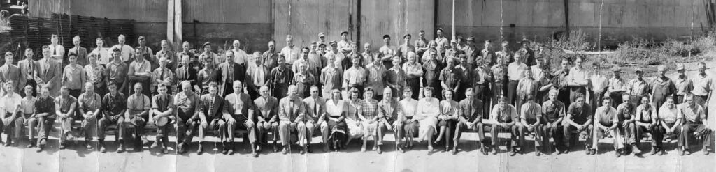 A panoramic black and white photograph of a group of men and women sitting and standing outside an industrial building.
