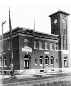 A black and white photograph of a brick building with semicircular arches and a tall square clocktower, stone stairs lead to the doors and streetcar tracks are in the road in front.