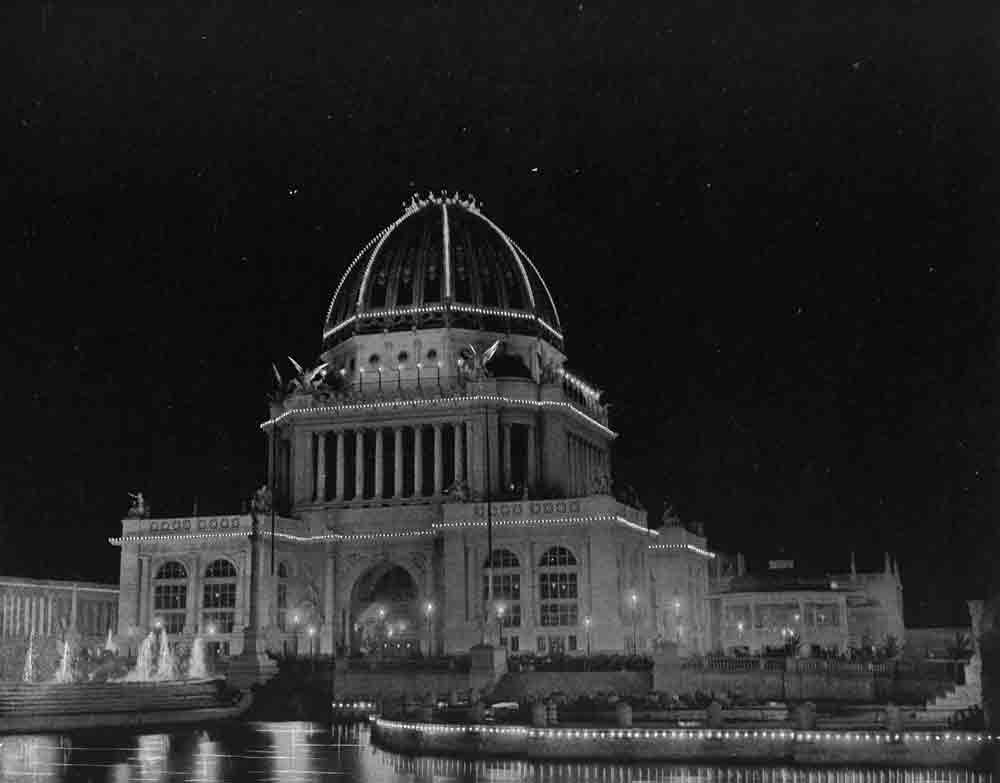 A black and white photograph of a domed building at night illuminated along its edges.