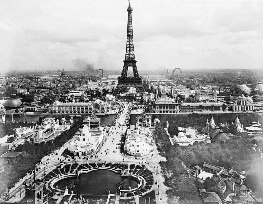 a black and white aerial photograph of the ground surrounding the Eiffel Tower in Paris.