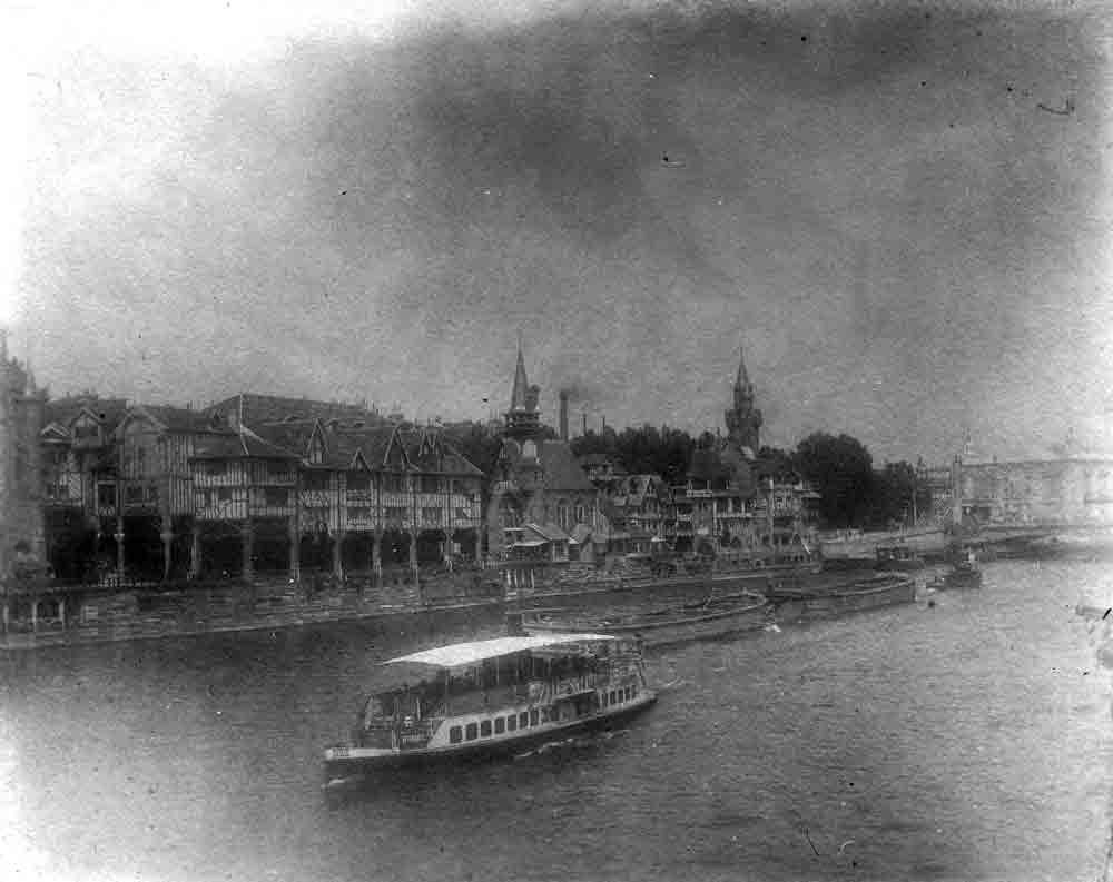 A black and white photograph of a covered boat moving down a river, timber framed buildings line the banks.